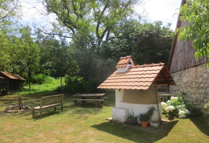 Prachtige tuin met uitzicht op brood en pizza oven bij luxe vakantiewoning in Kovácsszénája.
